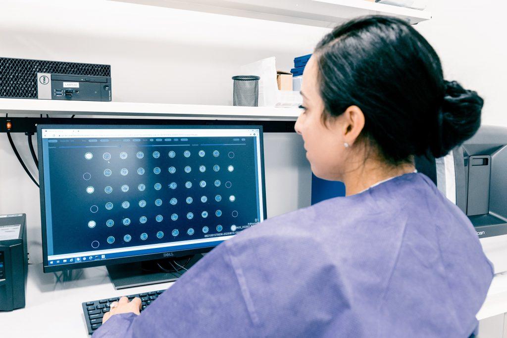 Lab tech scanning IMMray microarray slide
